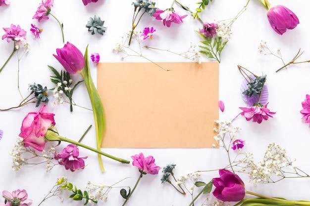Diferentes flores con papel en blanco sobre mesa.