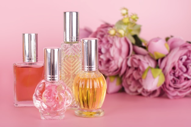 Diferentes frascos de perfume transparente con ramo de peonías sobre fondo rosa. botellas de esencia aromática