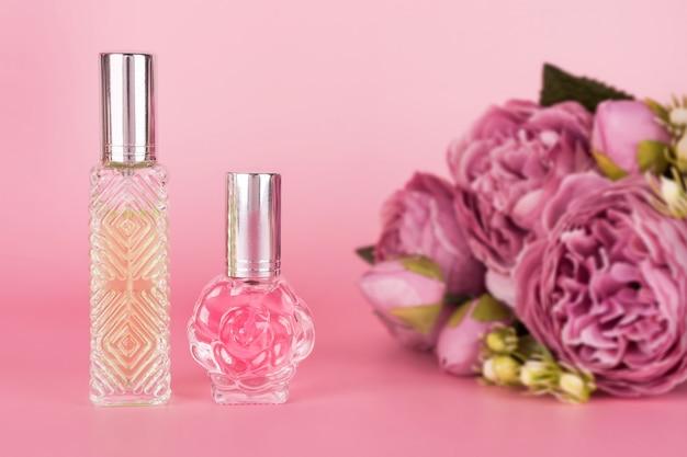 Diferentes frascos de perfume transparente con ramo de peonías sobre fondo rosa