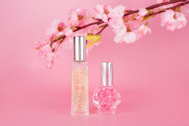 Diferentes frascos de perfume transparentes con rama de árbol floreciente primavera sobre fondo rosa. botellas de esencia aromática