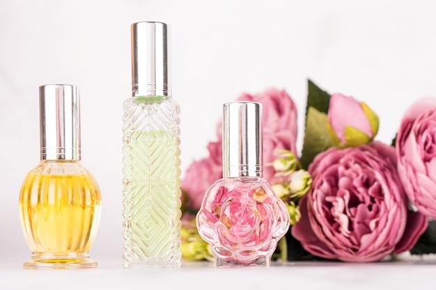 Diferentes frascos de perfume transparentes con ramo de peonías sobre fondo de mármol claro