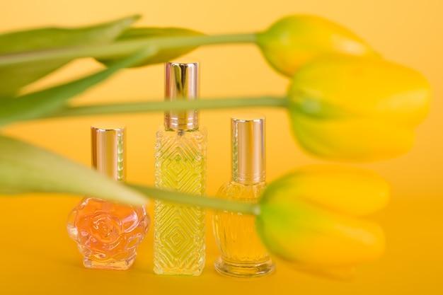 Diferentes frascos de perfume transparentes con ramo de tulipanes sobre fondo amarillo