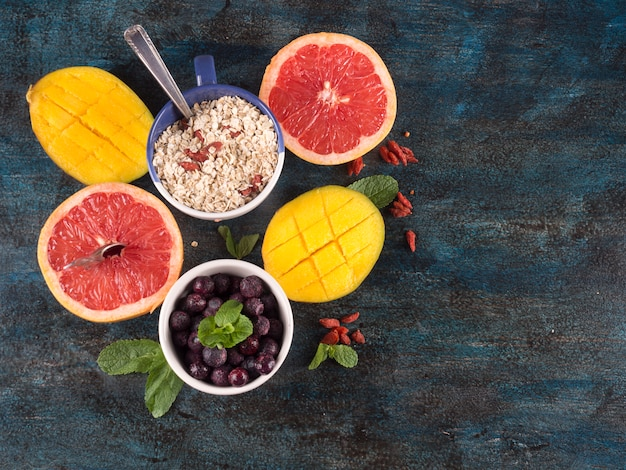 Diferentes frutas con avena en mesa azul