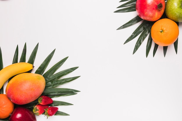Diferentes frutas tropicales en hojas de palmera.