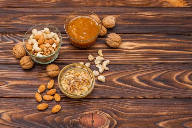 Diferentes frutos secos con miel en mesa de madera.