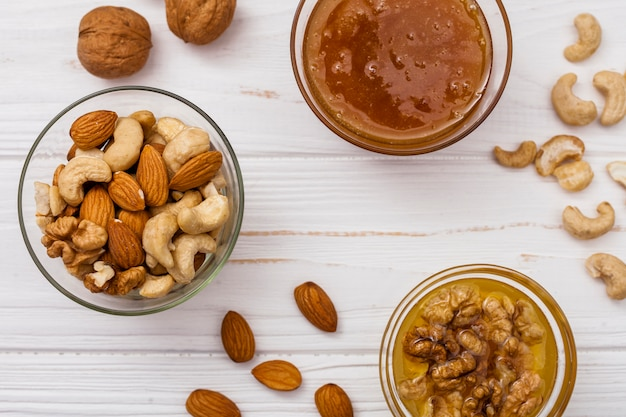 Diferentes frutos secos con miel en mesa.