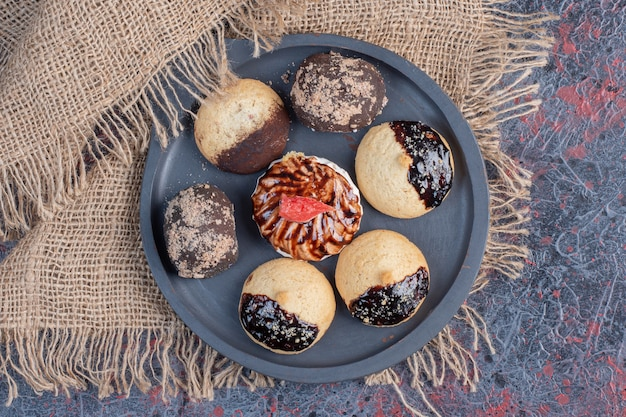Diferentes galletas dulces en placa negra