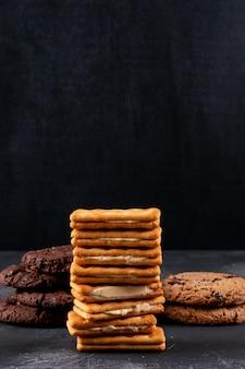 Diferentes galletas en superficie oscura