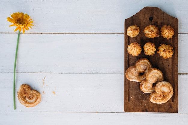 Diferentes galletas en tablero de madera con flor