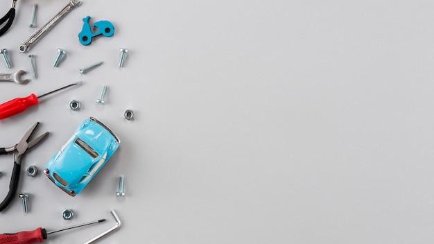 Diferentes herramientas con carro de juguete en mesa gris.