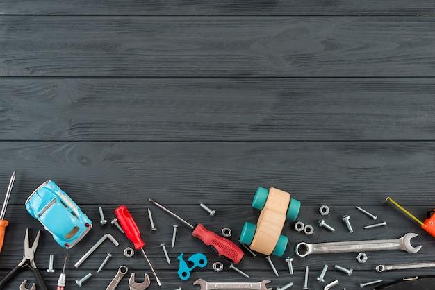 Diferentes herramientas con carro de juguete en mesa negra.