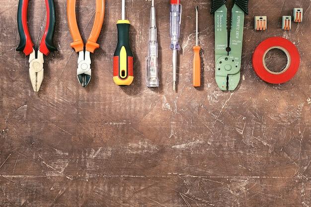 Diferentes herramientas eléctricas sobre fondo marrón claro con plase para texto, vista superior.