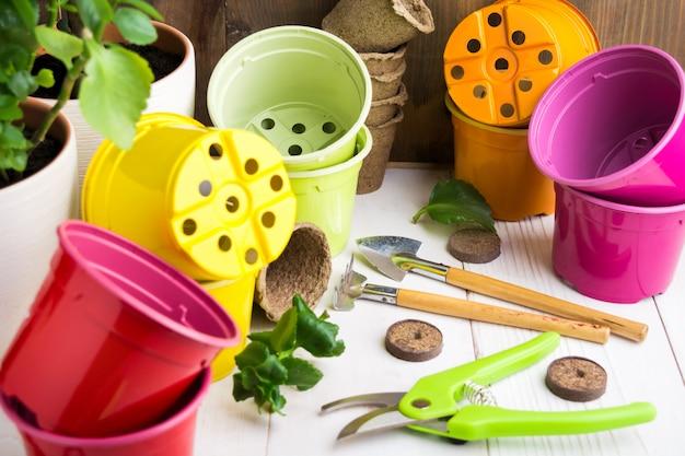 Diferentes herramientas de jardín y macetas de colores sobre una mesa de madera