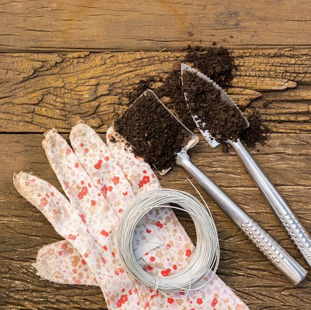Diferentes herramientas de jardinería en mesa de madera