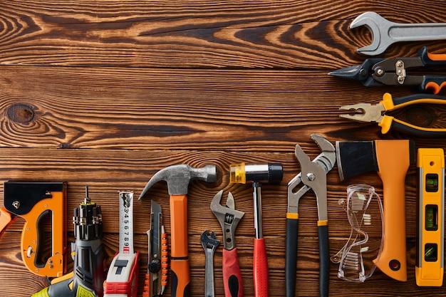 Diferentes herramientas de taller, mesa de madera. instrumento profesional, equipo de carpintero o constructor, destornillador y llave, pilas y tijeras de metal