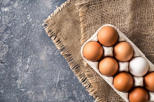 Diferentes huevos en caja de cartón sobre mesa de piedra oscura