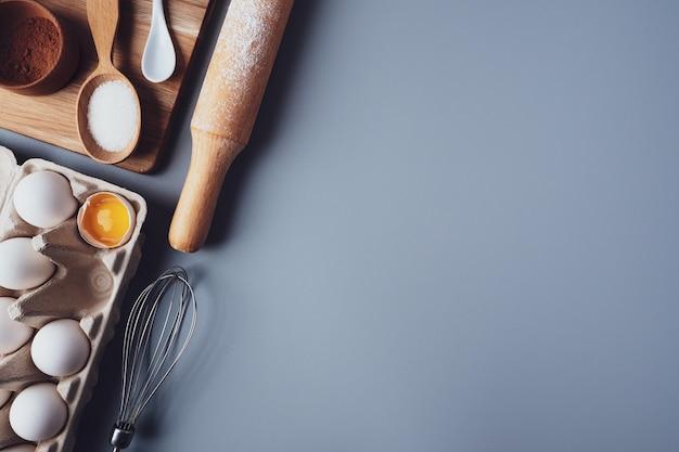 Diferentes ingredientes y utensilios de cocina para hacer galletas o cupcakes, plano, copyspace. huevos, rodillo, batidor, harina, moldes para galletas, diseño sobre un fondo gris. el concepto de repostería casera.