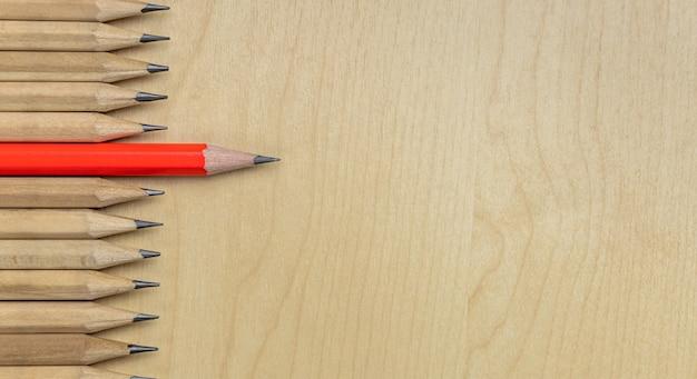 Diferentes lápices destacan el concepto de liderazgo. fondo de madera