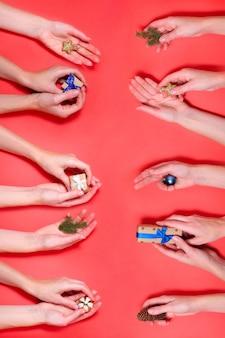 Diferentes manos sosteniendo elementos de navidad fondo rojo