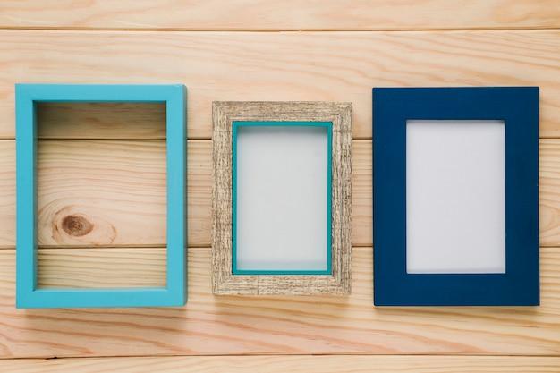 Diferentes marcos azules con fondo de madera.