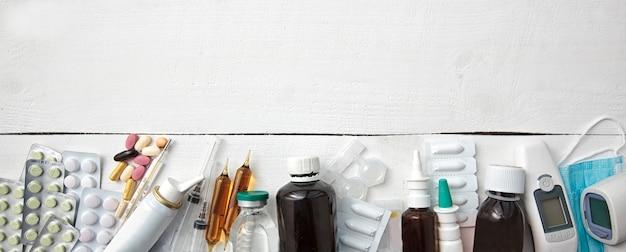 Diferentes medicamentos, píldoras y otros medicamentos en mesa blanca de madera