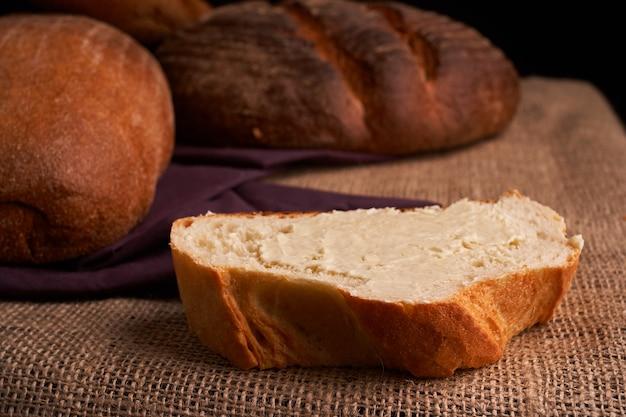 Diferentes pan y trigo en la mesa rústica. enfoque selectivo