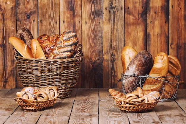 Diferentes panes con orejas en canasta sobre fondo de madera.