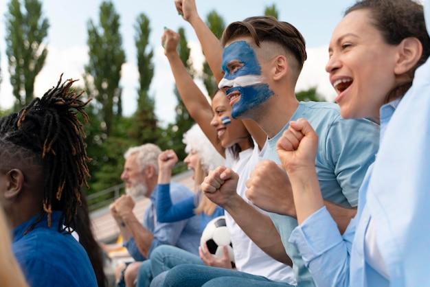 Diferentes personas mirando un equipo de fútbol.