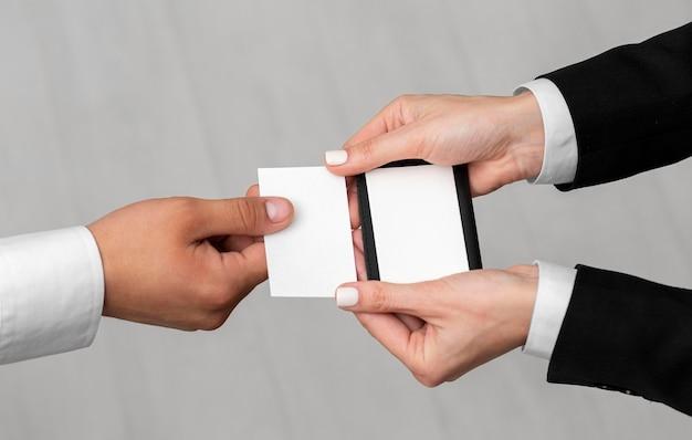 Diferentes personas sosteniendo una tarjeta de visita.