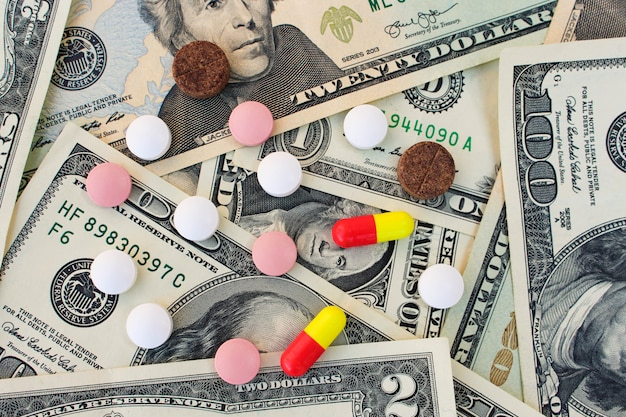 Diferentes píldoras médicas en billetes de un dólar