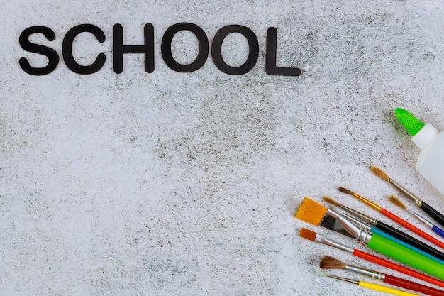 Diferentes pinceles sobre un fondo blanco con texto escolar. volver al concepto de escuela de arte.
