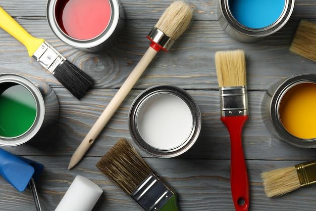 Diferentes pinturas, pinceles y rodillos sobre superficie de madera.