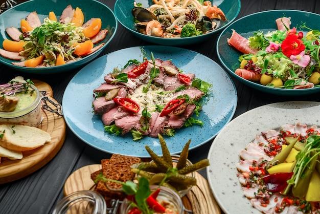 Diferentes platos en una mesa en un restaurante sobre un negro