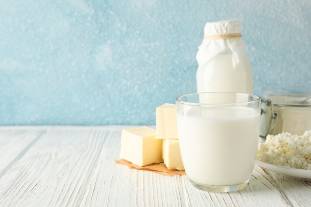 Diferentes productos lácteos en la mesa de madera blanca sobre fondo azul.
