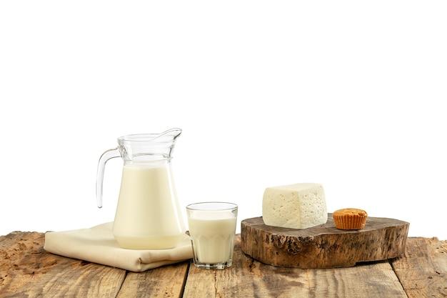 Diferentes productos lácteos, queso, crema, leche en mesa de madera y pared blanca. alimentación y estilo de vida saludables, nutrición natural orgánica, dieta. alimentos y bebidas deliciosas.