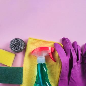 Diferentes productos de limpieza en fondo rosa