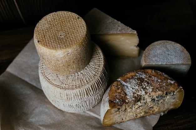 Diferentes quesos caseros en una mesa de madera oscura. piezas y cabezas de queso de gorgonzola, asiago, maasdam, gauda, paramezan y edam. queso de cabra y vaca sobre papel de horno. trabajo manual. de cerca