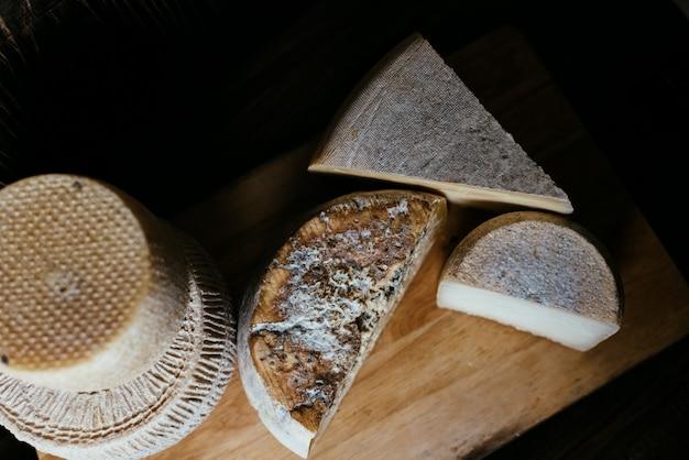 Diferentes quesos caseros en una mesa de madera oscura. piezas y cabezas de queso de gorgonzola, asiago, maasdam, gauda, paramezan y edam. vista superior.