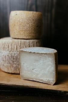 Diferentes quesos caseros en una mesa de madera oscura. piezas y cabezas de queso de kravot, manchego, paramezan. queso de cabra y vaca sobre papel de horno. trabajo manual. de cerca
