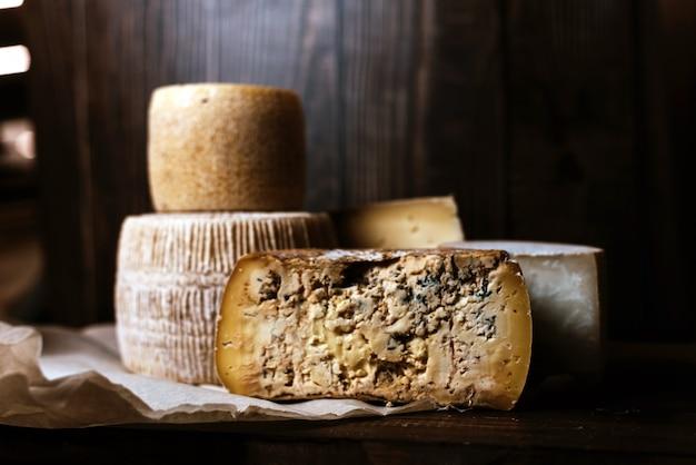 Diferentes quesos caseros en una pared de madera oscura. piezas y cabezas de queso de gorgonzola, asiago, maasdam, gauda, paramezan y edam. queso de cabra y vaca sobre papel de horno. trabajo manual. de cerca