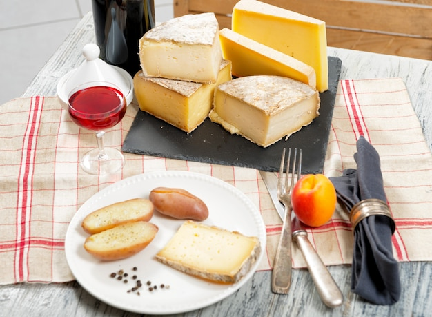 Diferentes quesos franceses con una copa de vino.