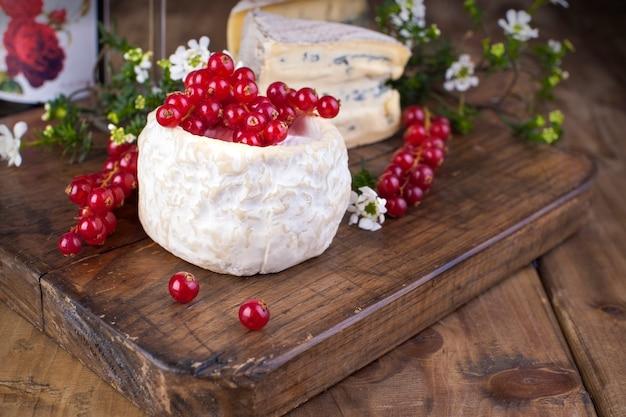 Diferentes quesos con moho y queso crema sobre una tabla de madera