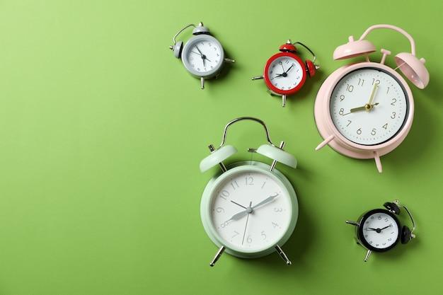 Diferentes relojes de alarma multicolores sobre superficie verde