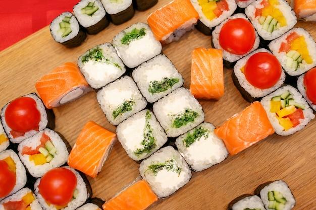 Diferentes rollos de sushi, con wasabi y jengibre en un plato sobre superficie de madera