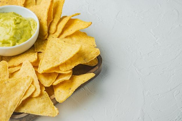 Diferentes salsas y salsas para nachos, sobre mesa blanca