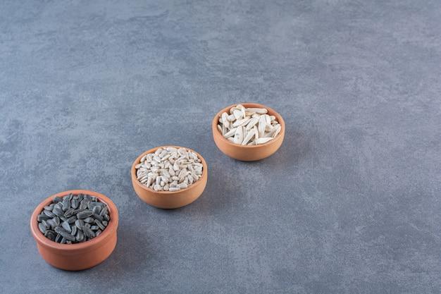 Diferentes semillas de girasol en tazones, sobre la superficie azul