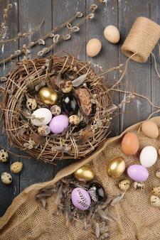 Diferentes tamaños huevos y plumas de colores pintados para pascua. boho stile. decoración alternativa