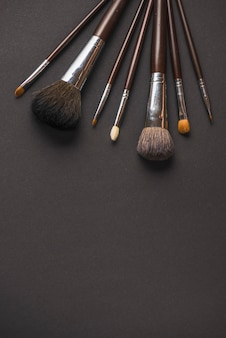 Diferentes tamaños de pinceles de maquillaje sobre fondo negro