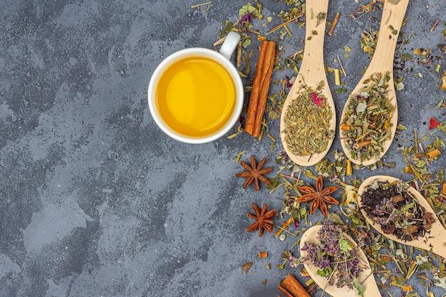 Diferentes tés secos en línea de cucharas de madera y taza de té