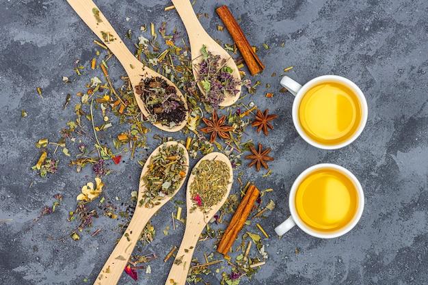 Diferentes tés secos en línea de cucharas de madera y tazas de té